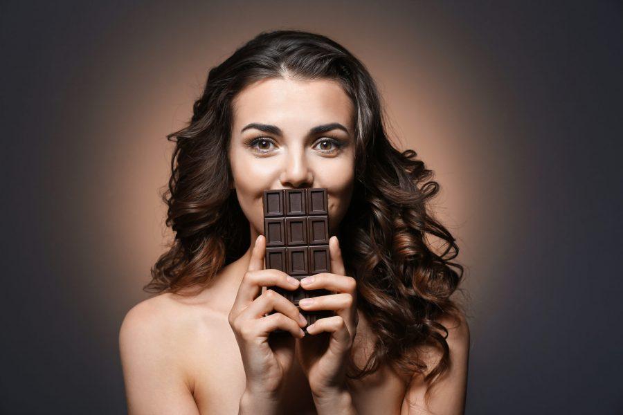 Beautiful girl with chocolate on dark background