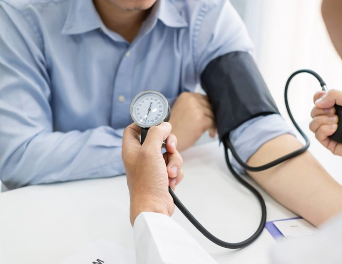 Doctor man is checking the blood pressure of the patient.