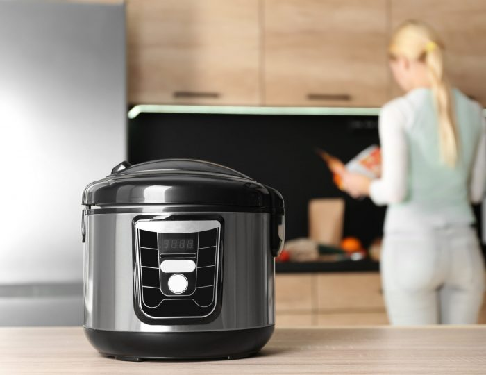 Modern multi cooker and blurred woman on background, space for text