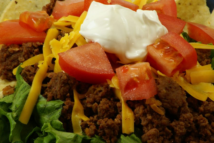 Homemade Mexican Meal: Taco Salad on blue fiesta style plate. Ground beef on bed of lettuce with corn chips, tomatoes, shredded cheddar cheese and sour cream.
