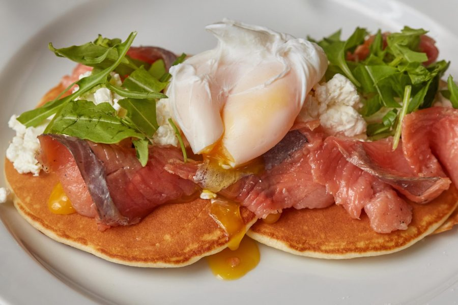 Breakfast of pancakes with salmon and egg florentine on plate, closeup