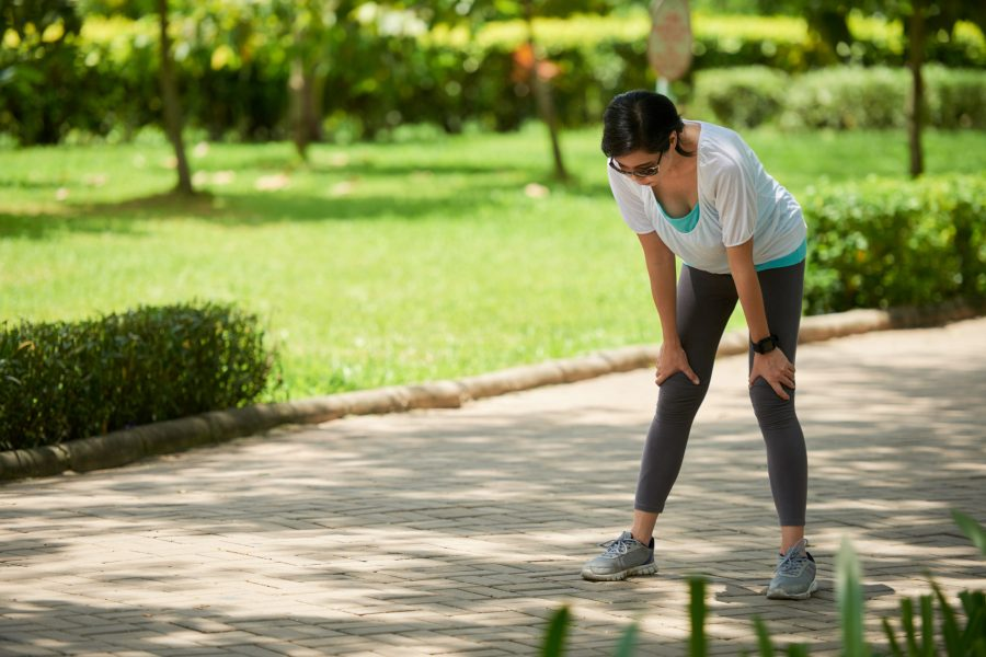 Portrait of adult Asian woman stopping to catch breath during jogging workout in park on sunny day
